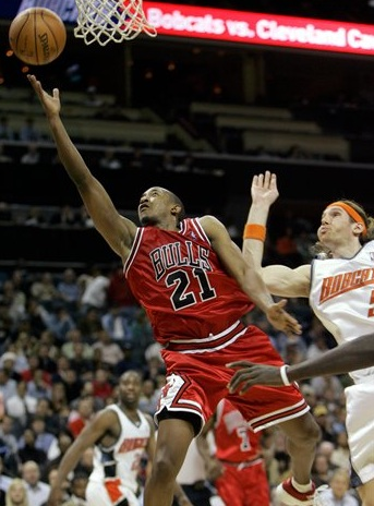 Chris Duhon of the Chicago Bulls shoots a layup while Walter Herrmann of the Charlotte Bobcats defends.