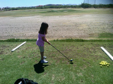 Young_golfer_at_practice_range_medium