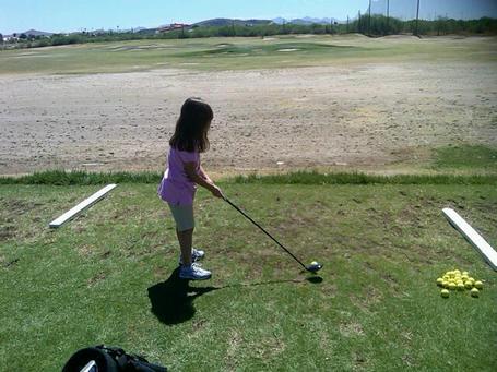 Young_golfer_at_practice_range_medium