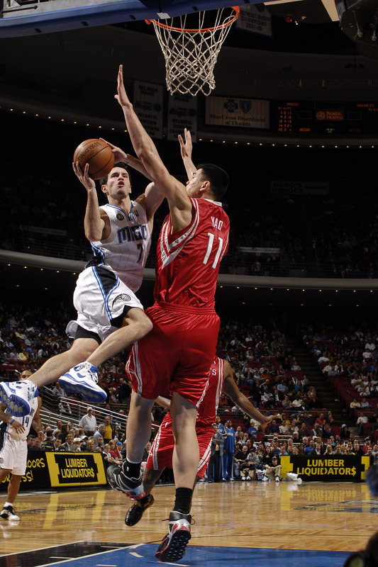 Orlando Magic guard J.J. Redick attempts a layup against Houston Rockets center Yao Ming in their NBA basketball game on November 22nd, 2008. The Rockets won, 100-95.