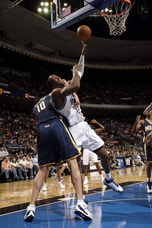 Dwight Howard of the Orlando Magic shoots a left-handed hook shot while being fouled by Jeff Foster of the Indiana Pacers on November 29th, 2008.