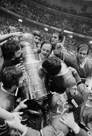 Montreal Canadien goalkeeper Ken Dryden gives the number one gesture while his teammates hug and kiss the Stanley Cup following their four-game sweep of the Philadelphia Flyers during the Stanley Cup Finals at the Spectrum Sports Arena. (1976) Click for source.