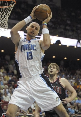 Marcin Gortat of the Orlando Magic grabs a rebound in front of Aaron Gray of the Chicago Bulls during Orlando's 107-79 win