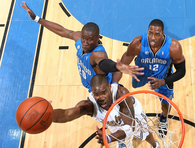 Mickael Pietrus of the Orlando Magic tries to block a layup attempt by Antawn Jamison of the Washington Wizards, wearing their throwback Chicago Zephyrs uniforms, in Orlando's 112-103 win on Friday, March 13th, 2009. Pietrus' teammate Dwight Howard looks on.